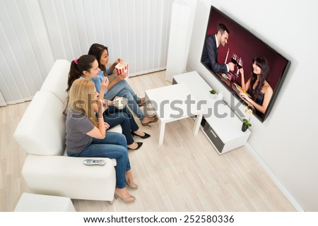 Multiethnic Young Women Sitting On Couch Watching Movie At Home - stock photo