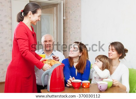 multigeneration family communicate over tea with cakes