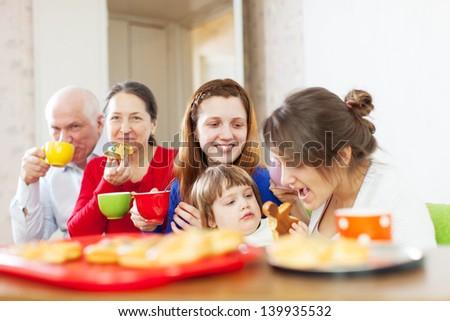 multigeneration family having tea with cakes at home - stock photo