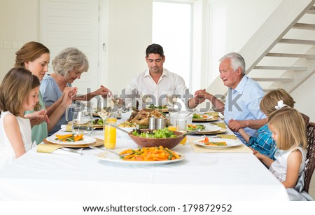 Multigeneration family praying together before meal at dining table - stock photo