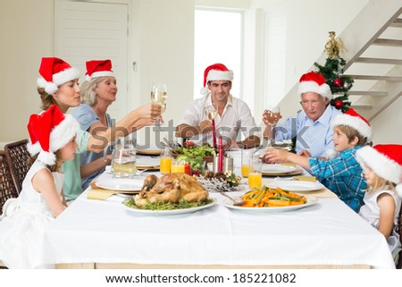 Multigeneration family toasting wine while having Christmas meal at home - stock photo