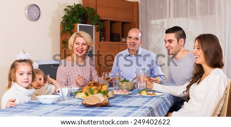 Multigenerational european family sitting at the table set for dinner
