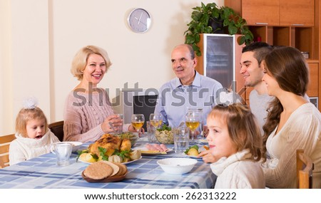 Multigenerational happy family sitting at the table set for dinner - stock photo