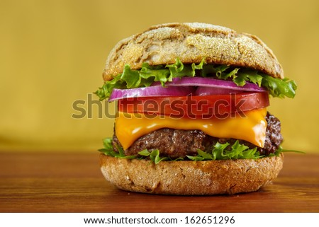 Multigrain bun hamburger on wooden table with yellow background