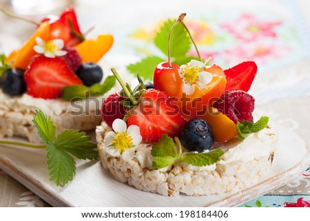 Multigrain rice cakes with berries, fruit and soft cheese for healthy breakfast - stock photo