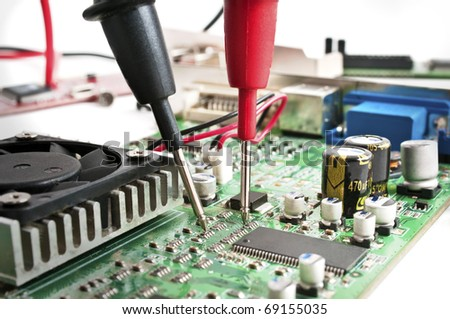 Multimeter probes examining a computer circuit board - stock photo