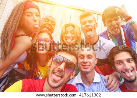 Multinational football supporters taking selfie outdoors - Happy multiracial people making funny faces on camera for olympic games - Sport against racism concept - Focus on bottom left guy  - stock photo