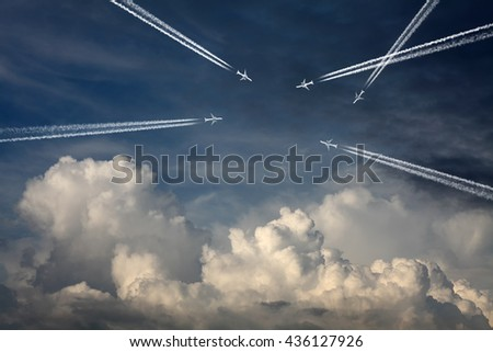 Multiple airplane creating exhaust contrails across a blue cloudy sky for the concept of a crowded airspace. - stock photo