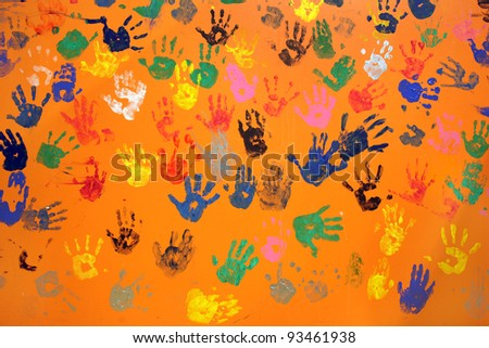 multiple colored hand prints on orange background