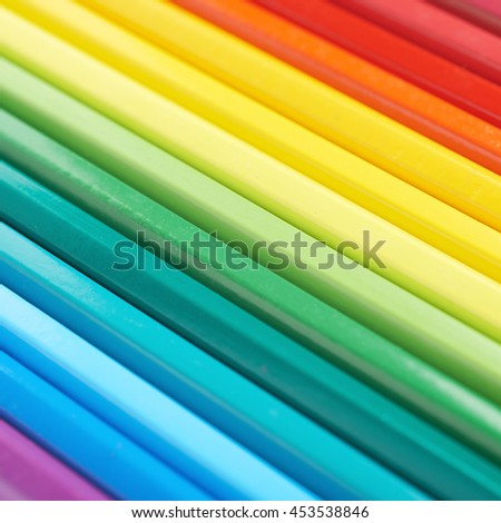 Multiple colorful color pencils composition arranged in a line to form a rainbow gradient, close-up crop fragment - stock photo
