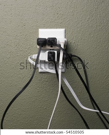 Multiple electrical plugs in wall outlet - stock photo