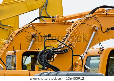 Multiple Excavator Boom Arms Showing Hydraulic Hoses - stock photo