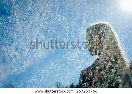 Multiple exposure image of pretty girl standing in the field on blue sky copy space background - stock photo