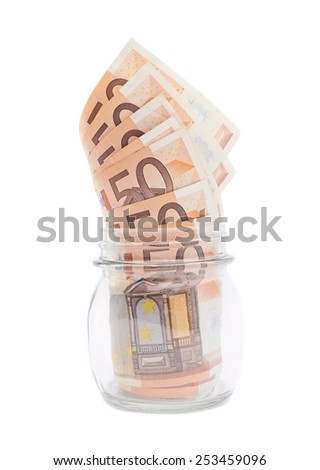 Multiple fifty euro bank notes in a glass jar isolated over the white background
