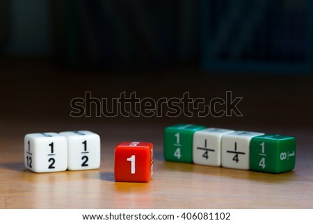 Multiple fraction dices on wood table, shown in red white and green color with quarters, halves, and whole numbers against dark background - stock photo