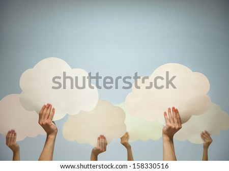 Multiple hands holding cut out paper clouds against a blue background - stock photo