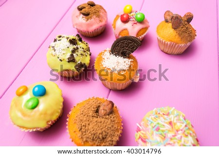 Multiple muffins decorated with multicolored frosting, cocoa powder and beans, candies and whipped cream top view toned selective focus - stock photo