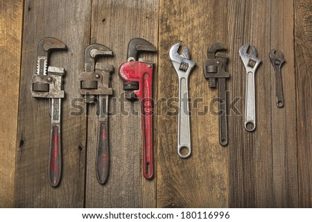 Multiple Pipe Wrenches On Wood Background - stock photo