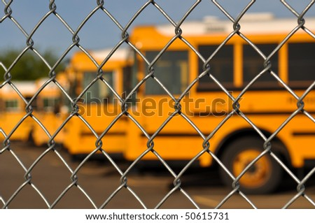 Multiple School Bus with Blue Sky background behind fence - stock photo