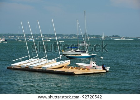 Multiple small training sailboats or skiffs sitting on offshore dock waiting on the weekend sailors to train