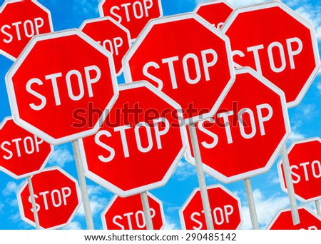 Multiple stop sign against blue sky background  - stock photo