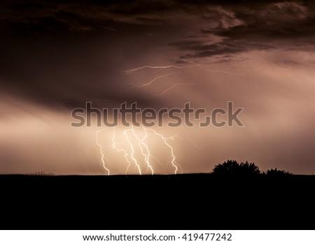 Multiple streaks of lightning at night against the ground. - stock photo