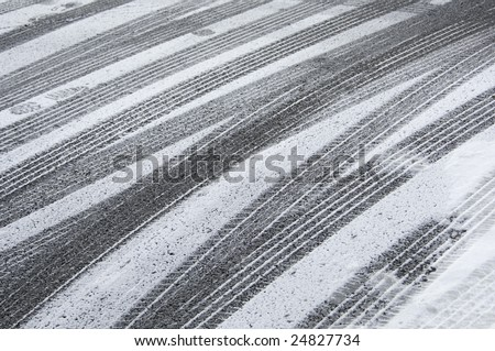 Multiple tracks of car tires, with a few footprints, in snow on pavement - stock photo