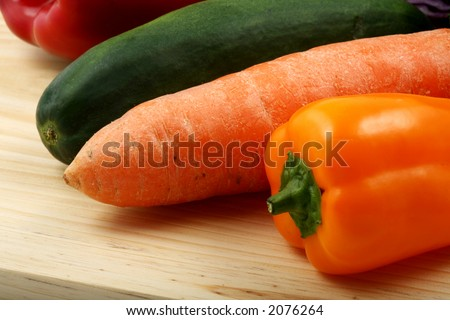 Multiple vegetables on a wood table in an oblique view.