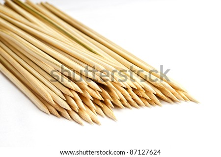 Multiple wooden bamboo skewers laying on white background - stock photo