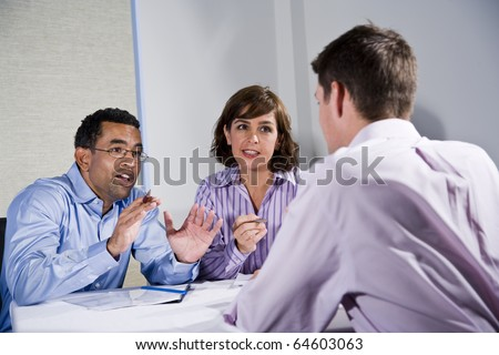 Multiracial business meeting in boardroom, sitting at a table - stock photo