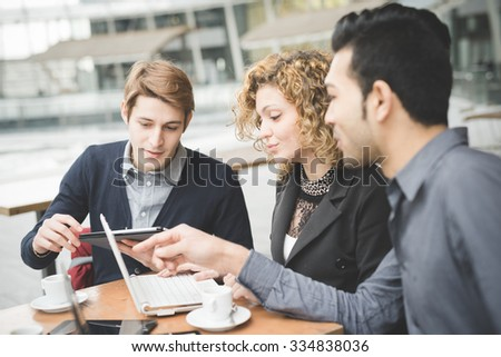 Multiracial business people working connected with technological devices at the bar - stock photo