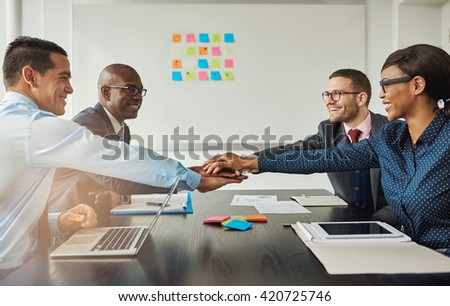 Multiracial business team signalling their commitment to each other by reaching across the table in the office to stack hands as they smile at each other - stock photo
