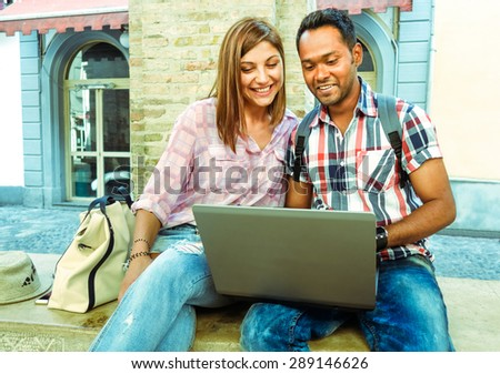 Multiracial business young couple with laptop connected wifi - Attractive mixed happy students having fun with pc technology  - Best friends ethnic lovers surfing web - Concept of youth against racism - stock photo