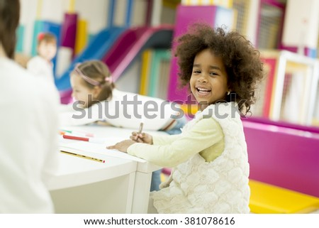 Multiracial children drawing in the playroom - stock photo