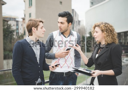 Multiracial contemporary business people working outdoor in town connected with technological devices like smartphone and tablet, talking to each other  - business, finance, technology concept - stock photo