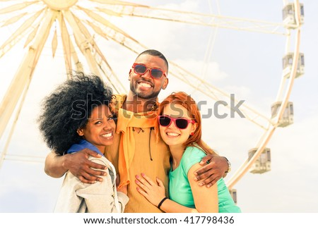 Multiracial friends having fun at ferris wheel park  - Happy multiethnic students  smiling  at photo camera background funfair - Concept of people joyful moment happiness and travel around the world - stock photo