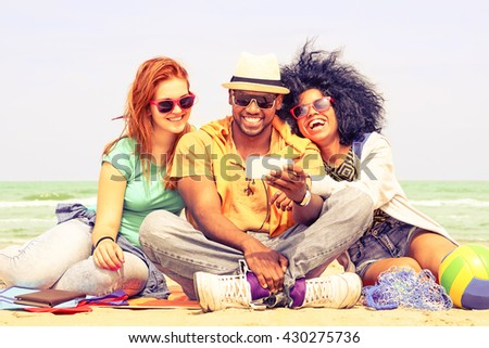 Multiracial friends having fun watching travel video at the beach - Happy group of students using mobile phone by the ocean - Concept of friendship and new technologies - Nostalgic vintage filter look - stock photo
