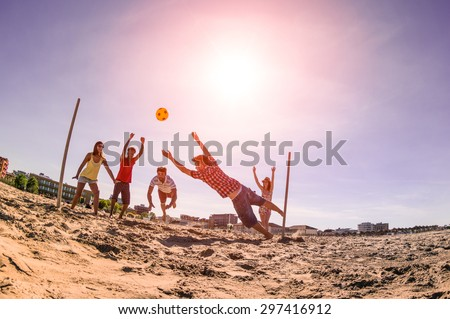 Multiracial friends playing soccer at beach - Concept of multi cultural friendship having fun with summer games - Backlight marsala filter with late afternoon sunshine halo and fisheye lens distortion - stock photo