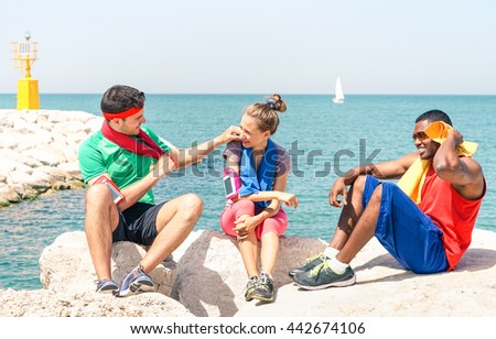 Multiracial friends relaxing after fitness on the beach - Multicultural young teens sitting at  pier rocks with ocean background in hot summer training day - Concept of friendship and healthy life - stock photo