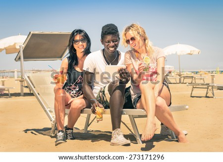 Multiracial friendship with smiling guy with girlfriends drinking cocktails with tablet pc at the beach - Modern concept of vacations with friends having fun enjoying wifi internet in the summer - stock photo
