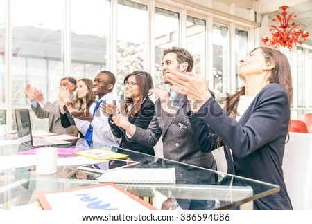 Multiracial group of business people clapping hands to congratulate their boss - Business company team, standing ovation after a successful meeting - stock photo
