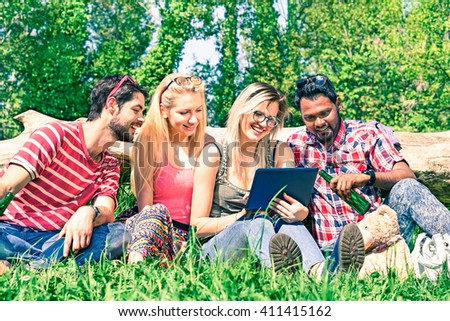 Multiracial group of cheerful friends having fun with pc at city park - Happy students sitting on green grass using laptop in positive social moment at spring - Summer concept of joy youth and leisure