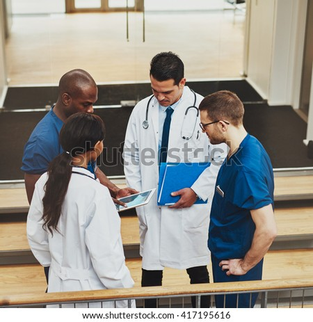 Multiracial group of doctors in an impromptu meeting standing on a stairwell looking at information on a tablet computer, view from above - stock photo
