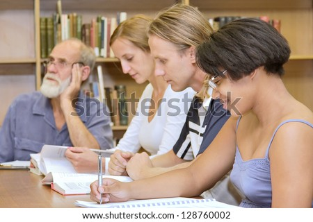 Multiracial group of four people studying in library. Shot in South Africa. - stock photo