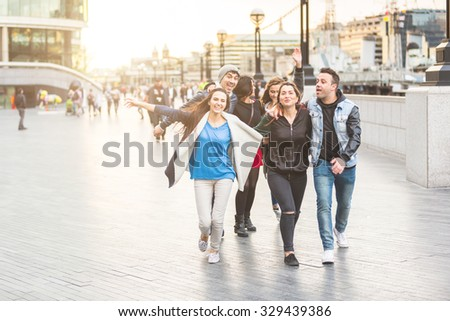 Multiracial group of friends enjoying their time in London. They are four women and two men in their twenties, they are walking, laughing and having fun together. Friendship and lifestyle concepts. - stock photo