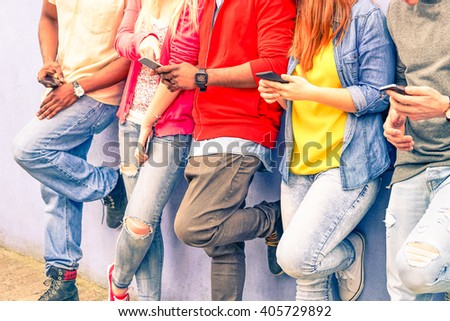 Multiracial group of friends texting sms and looking down to cell phone - Interracial students hands using mobile - Concept of young people addiction to web technology - Focus on hand of red hair girl - stock photo