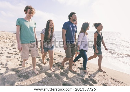 Multiracial Group of Friends Walking at Beach - stock photo