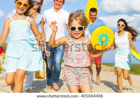 Multiracial group of friends with children walking at the beach - stock photo