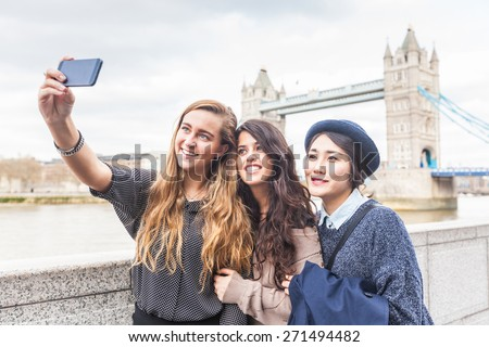Multiracial group of girls taking a selfie in London with Tower Bridge on background. The group consists of three girls, one is from Korea, one from Spain and one from Holland - stock photo