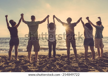 Multiracial group of people with raised arms looking at sunset. Backlight shot. Happiness, success, friendship and community concepts.
